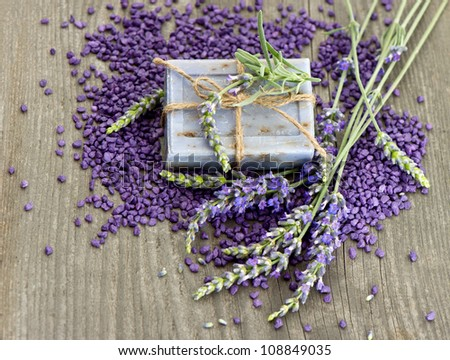 herbal lavender soap and bath salt with fresh flowers over wooden background