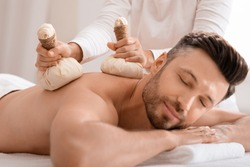 Herbal massage concept. Unrecognizable spa attendant making body massage for handsome man with herbal compress balls, luxury spa interior. Man enjoying herbal treatment at massage salon