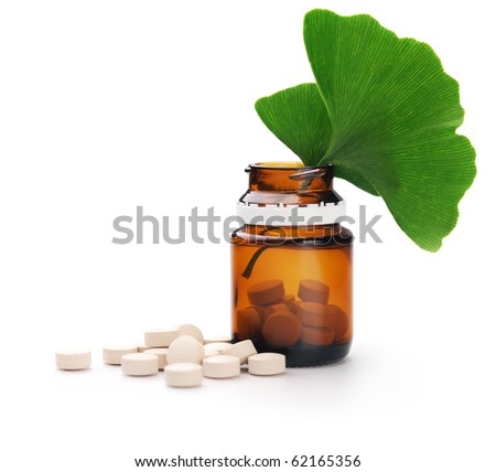 Herbal medicine. Ginkgo leaves and tablets n a bottle. Isolated over white background