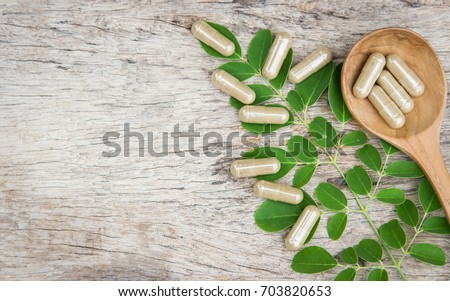 Herbal medicine in capsules from moringa leaf on rustic wooden table with copy space for medical background, healthy eating with natural product for good living