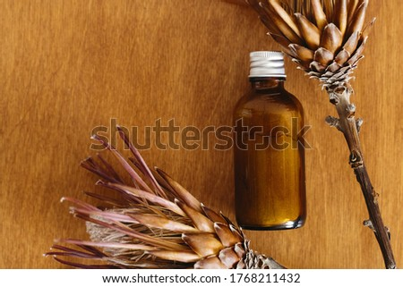 Herbal organic ubtan in glass bottle on wooden background with dried protea flowers, flat lay. Ubtan ayurveda. Plastic free hygiene items. Zero waste cosmetics