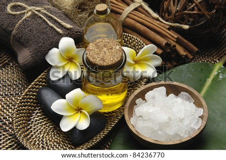 herbal salt in bowl with frangipani flowers and massage oil with green leaf on mat