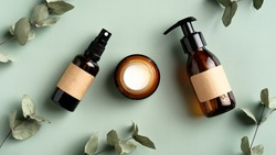 Herbal skincare cosmetics set and eucalyptus leaves on green background. Amber glass body spray bottle, liquid soap dispenser, moisturizer cream jar. SPA natural organic beauty products design.
