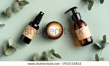 Herbal skincare cosmetics set and eucalyptus leaves on green background. Amber glass body spray bottle, liquid soap dispenser, moisturizer cream jar. SPA natural organic beauty products design. Сток-фото ©