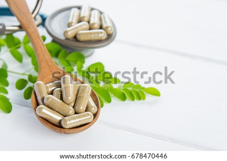 Herbal supplement in capsules with stethoscope on white table for healthy  medicine living