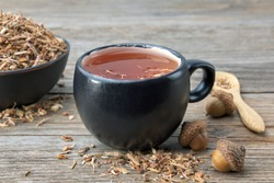Herbal tea cup, healthy oak bark in black ceramic bowl and acorns on wooden table. Herbal medicine.