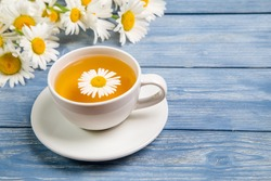 Herbal tea from chamomile flowers and a bouquet of daisies on a blue background. The concept of healthy tea.