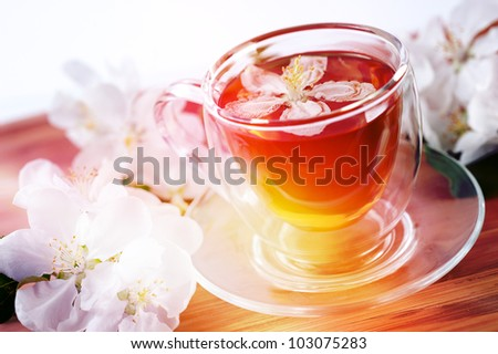 Herbal tea in a glass bowl with flowers of apple
