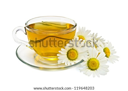 Herbal tea in a glass cup and saucer, a bouquet of chamomiles isolated on white background