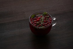 Herbal tea in a glass mug on a wooden table. Hot drink with mint, ginger and lingonberry. Berry tea close-up, place for text, background.