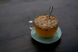 Herbal tea in a glass mug on a wooden table. Hot drink with mint, ginger and sea buckthorn . Berry tea close-up, place for text, background.