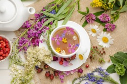 Herbal tea in a white cup on a white wooden table with flowers. Tea ceremony. Blooming Sally.