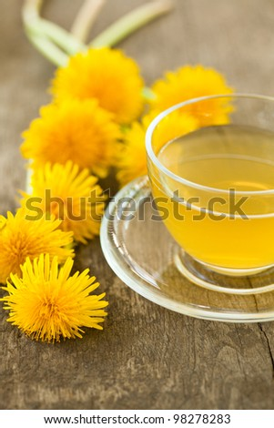 Herbal tea in glass cup and flowers on wooden table