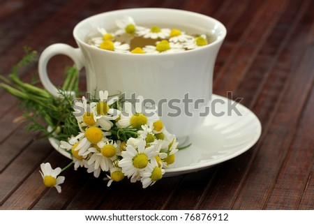 herbal tea with chamomile on a wooden table ,shallow dof