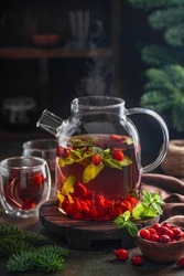 Herbal tea with mint and rose hips in a glass teapot on the table. Winter vitamin warming tea. Selective focus