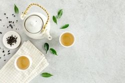 Herbal tea with two white tea cups and teapot, with green tea leaves. Flat lay, top view. Tea concept