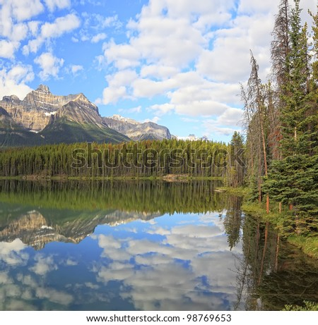 Herbert Lakes with reflection of the cloudy sky and snow mountains in a smooth water  (Banff National Park, Alberta, Canada)