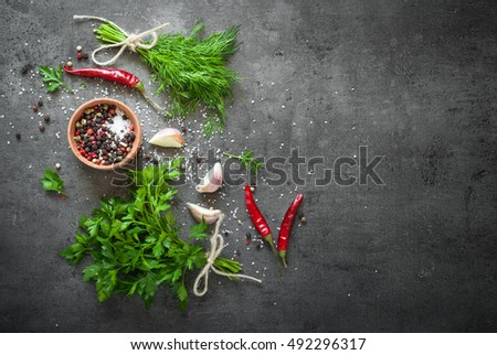Herbs and spices at dark slate table. Parsley, dill, garlic and pepper. Ingredients for cooking.