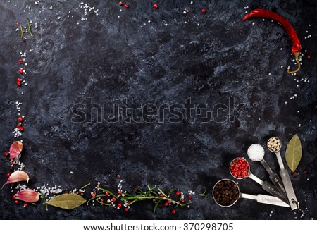 Herbs and spices frame over black stone background. Top view with copy space