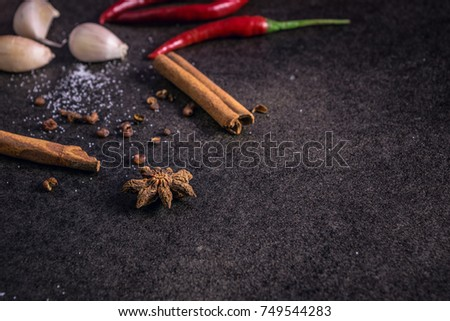 Herbs and spices over black stone background, mystic photography,  selective focus and dark background #749544283