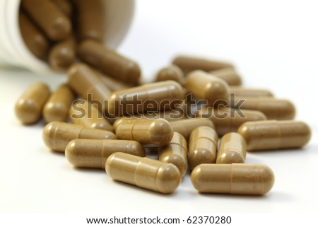 Herbs capsules spilling out of a bottle. Isolated on white background.