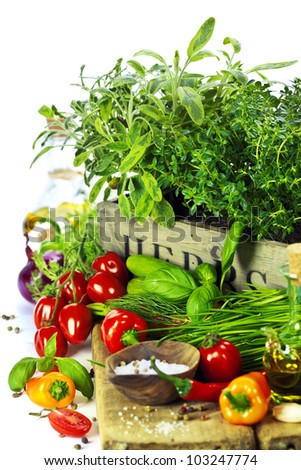 herbs in the box and fresh vegetables over white