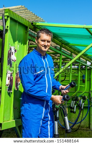 Herdsman standing in front of a machine milking cows