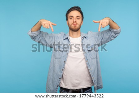Here and right now! Portrait of bossy tyrant man in denim shirt pointing down and looking with arrogance, demanding immediate submission, demonstrating authority. indoor studio shot, blue background ストックフォト ©