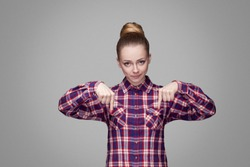 Here and right now. serious angry blonde girl in red, pink checkered shirt, collected bun hairstyle standing and looking at camera and pointing down. indoor studio shot. isolated on gray background