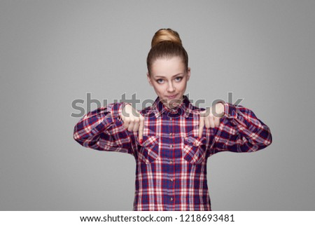 Here and right now. serious angry blonde girl in red, pink checkered shirt, collected bun hairstyle standing and looking at camera and pointing down. indoor studio shot. isolated on gray background #1218693481