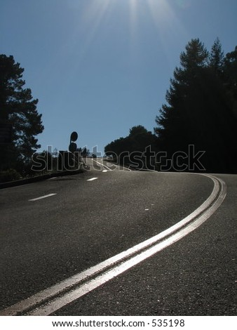 Here is an upward winding road in Northern California.  On this day the sun shone in such a way that the stripes on the road appeared silver. #535198