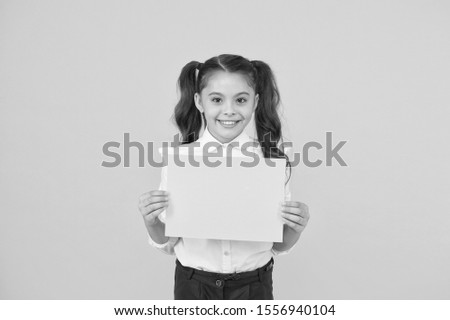 Here is your homework. Adorable small child holding empty homework sheet on yellow background. Cute little girl with blank green school paper for doing homework assignment. Homework, copy space.