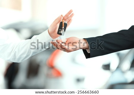 Here is your key. Closeup of man giving key to the car owner while standing in front of a car