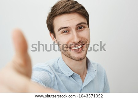 Here, let me lend you hand. Portrait of charming friendly caucasian man pulling hand towards camera as if trying to grab it or help girlfriend get down, smiling broadly over gray background Stock fotó ©