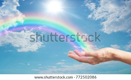 Here's a Rainbow  for You - female hand with a bright rainbow arcing across a blue sky with fluffy clouds and a bright sun burst