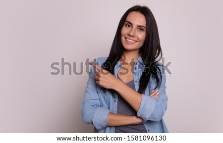 Here she is. Close-up photo of a lovely girl with long dark hair, who is smiling  and posing with folded arms, pointing with her left hand to the left upper corner. #1581096130