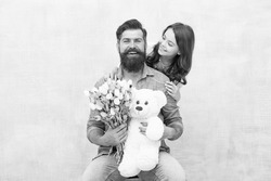 Heres to celebrating you. Happy family celebrate birthday. Little girl congratulate bearded man. Small daughter and father hold flowers and toy. Birthday anniversary. Happy birthday to you.