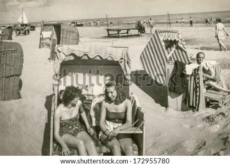 HERINGSDORF, GERMANY, CIRCA 1956 - Vintage photo of women in beach basket - stock photo