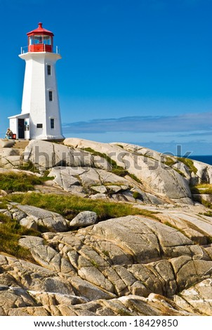 Heritage lighthouse on a rocky beach. Peggy's Cove, Canada.