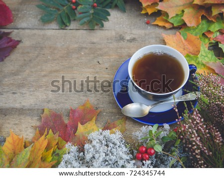Hero header image cup of hot tea with spoon on vintage wooden table and autumn maple leafs