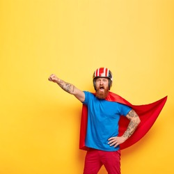 Heroic male character dressed in superhero suit, shouts with courage I am ready to fly, makes flight gesture, saves people, makes world better place, fights against difficulties, poses indoor
