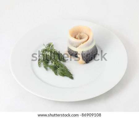 Herring and dill in white plate.