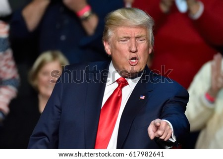 """HERSHEY, PA - DECEMBER 15, 2016: President Donald Trump dynamic pointing toward the crowd at a """"Thank You Tour"""" rally held at the Giant Center."""