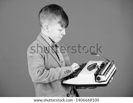Hes going to write a composition. Smart child writer. Little writer typing on retro typewriter. Cute boy writer working on mechanical desktop typewriter. Small writer composing story.