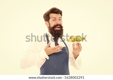 Hes mean cook. Bearded man present dish. Professional cook isolated on white. Chef in cook apron. Food cooking and preparation. Restaurant and canteen. Food catering. Cook will give you dinner.