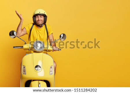 Hesitant young man has clueless expression, raises palm with doubt, wears yellow t shirt, protective helmet, rides fast motorcycle, isolated over yellow background, thinks which way to choose