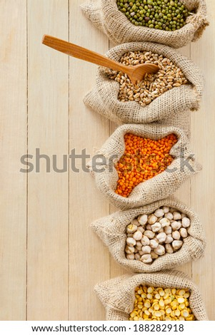 hessian bags with peas, chick peas, red lentils, wheat and green mung on table, top view
