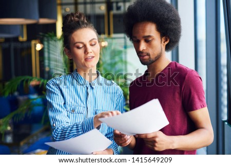 Heterosexual couple analyzing important documents in the office   #1415649209