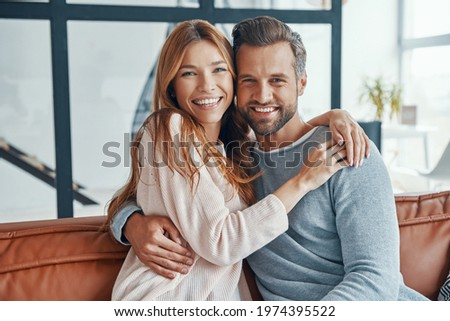 Heterosexual couple smiling and looking at camera while spending time at home Сток-фото ©