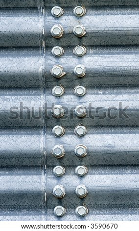 Hex-head bolts connecting two corrugated steel panels of a grain storage silo.